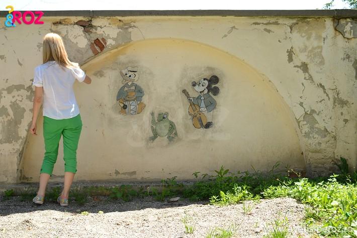 fata cu pantaloni verzi desenand pe perete